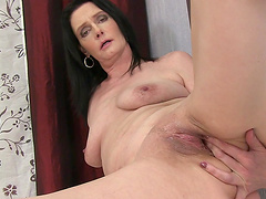 Horny solo mature Laura Dark takes off her jeans to masturbate